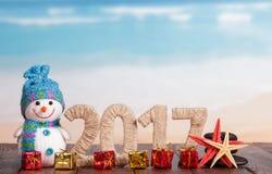 Les schémas noix de coco 2017, étoiles de mer et table de cadeaux de Noël contre la mer Photographie stock