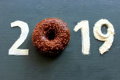 Les schémas 2019 sur un fond noir ont rempli de la farine, beignet rose au lieu du numéro 0, le concept de la nouvelle année, la  images stock