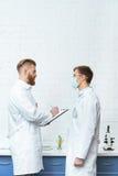 Les scientifiques dans des manteaux blancs discutant l'expérience a comme conséquence le laboratoire Photo libre de droits