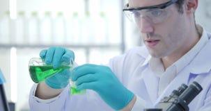 Les scientifiques de recherches médicales mélange les liquides de tabagisme dans des bechers banque de vidéos