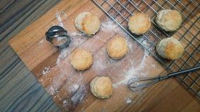 Les scones crèmes anglaises sur le conseil en bois avec le coupeur et battent Photos stock