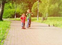 Les scooters d'équitation de fille de petit garçon et d'enfant en bas âge en été se garent Photographie stock