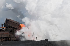 Les scories fondues liquides et un nuage de vapeur chaude Photographie stock
