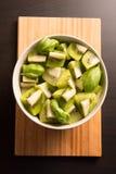 Les segments découpés en tranches de kiwis avec le basilic part dans une cuvette ronde Image libre de droits