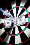 Les seringues et l'argent ont collé sur un dartboard Photo libre de droits