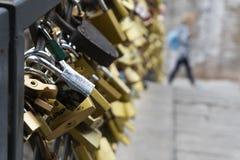 Les serrures ont attaché aux balustrades du pont comme symbole de l'amour Photos stock