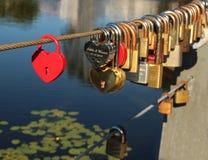 Les serrures rouges au coeur forment sur le pont de corde Photos libres de droits