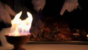 Les serveurs coupent en tranches des morceaux de viande La cuvette du feu qui éclaire la coupe des serveurs de viande Le chef Coo banque de vidéos