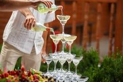 Les serveurs versent le champagne sur une pyramide des verres à vin Image libre de droits