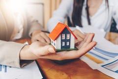 Les services d'immobiliers pour la maison de achat tient le modèle et le calcu de maison photo libre de droits