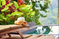Les serviettes avec le frangipani blanc fleurit près de la piscine Image stock