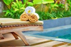 Les serviettes avec le frangipani blanc fleurit près de la piscine Photos stock