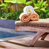 Les serviettes avec le frangipani blanc fleurit près de la piscine Photo libre de droits