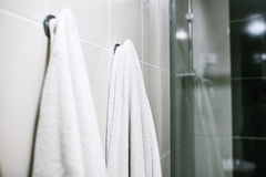 Les serviettes blanches accrochent sur le mur dans la salle de bains Propreté, douche photo stock