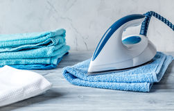 Les serviettes empilent avec du fer dans le ménage réglé sur le fond laudry image libre de droits
