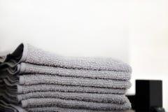 Les serviettes grises de serviettes sont sur le plancher de salle de bains Serviettes accrochées sur des crochets image libre de droits