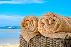 Les serviettes ont roulé sur une table de canne à la plage Photo libre de droits