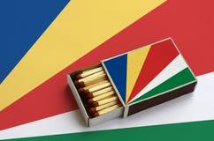 Les Seychelles diminuent sont montrées dans une boîte d'allumettes ouverte, qui est remplie de matchs et se trouve sur un grand d photos stock