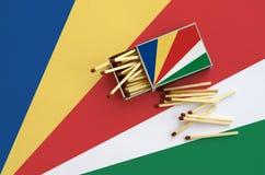 Les Seychelles diminuent sont montrées sur une boîte d'allumettes ouverte, de laquelle plusieurs matchs tombent et des mensonges  photos libres de droits