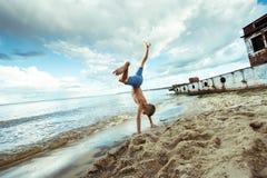 Les shorts de garçon est des sauts heureux et renverse sur la plage Photographie stock libre de droits