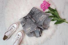 Les shorts en lambeaux gris, les espadrilles blanches et la pivoine fleurissent Concept à la mode, fourrure blanche sur le fond Images libres de droits