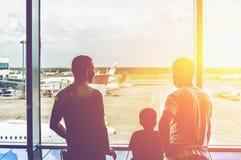 Les silhouettes de deux hommes et enfants dans le terminal d'aéroport, voyageuses de personnes regardent des avions Images stock