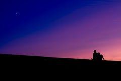 Les silhouettes de deux hommes s'asseyant, au coucher du soleil Photos stock