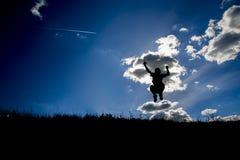 Les silhouettes de jeune sauter de garçon Image stock