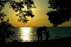 Les silhouettes de la femme et du garçon sur le coucher du soleil à la mer aboient Photo stock