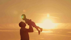Les silhouettes de père et de fils jouent à la plage de coucher du soleil Image libre de droits