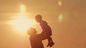Les silhouettes de père et de fils jouent à la plage de coucher du soleil Photo stock