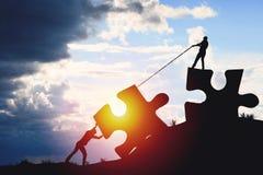 Les silhouettes de personnes mettant le puzzle rassemble sur la lumière du soleil Photo stock