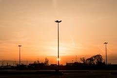 Les silhouettes de trois lampadaires d'éclairage routier forment une perspective d'une triangle contre le coucher du soleil au-de Image libre de droits