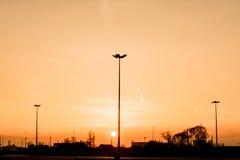 Les silhouettes de trois lampadaires d'éclairage routier forment une perspective d'une triangle contre le coucher du soleil au-de Photographie stock libre de droits