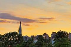 Les silhouettes des bâtiments et des gratte-ciel modernes sur l'arrangement du fond OD ou Soleil Levant à Pétersbourg Photos stock