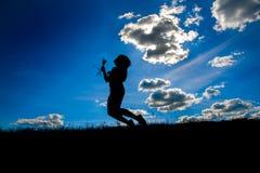 Les silhouettes des femmes tenant des fleurs et volant sur l'une colline principale Image libre de droits