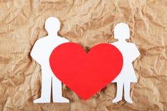 Les silhouettes des hommes, des femmes et du coeur ont coupé du papier. Image stock