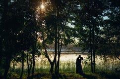 Les silhouettes des jeunes mariés embrassent sur le rivage du lac entre les arbres au coucher du soleil Photographie stock