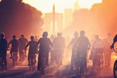 Les silhouettes des personnes sur des bicyclettes sur le coucher du soleil dans la ville se garent Images libres de droits