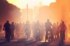 Les silhouettes des personnes sur des bicyclettes sur le coucher du soleil dans la ville se garent Image libre de droits
