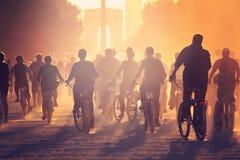 Les silhouettes des personnes sur des bicyclettes sur le coucher du soleil dans la ville se garent Image stock