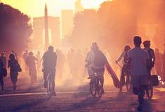 Les silhouettes des personnes sur des bicyclettes sur le coucher du soleil dans la ville se garent Images stock
