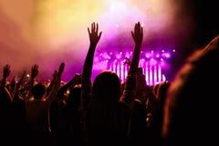 Les silhouettes du concert se serrent dans l'avant sur les lumières lumineuses d'étape Images libres de droits