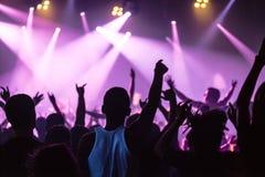 Les silhouettes du concert se serrent devant les lumières lumineuses d'étape Photographie stock