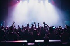 Les silhouettes du concert se serrent devant les lumières lumineuses d'étape Photographie stock libre de droits