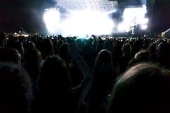 Les silhouettes du concert se serrent devant les lumières lumineuses d'étape Fond foncé, fumée, projecteurs de concert Image stock