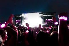 Les silhouettes du concert se serrent devant les lumières lumineuses d'étape Fond foncé, fumée, projecteurs de concert Photographie stock libre de droits