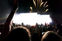Les silhouettes du concert se serrent devant les lumières lumineuses d'étape Fond foncé, fumée, projecteurs de concert Photos libres de droits