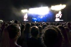 Les silhouettes du concert se serrent devant les lumières lumineuses d'étape Fond foncé, fumée, projecteurs de concert Image libre de droits