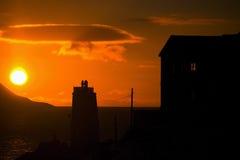 Les silhouettes du coucher du soleil orange-foncé Photo libre de droits